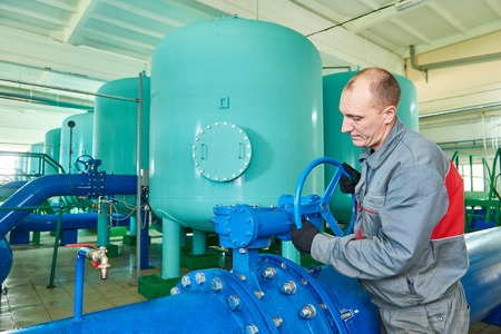 filtration: Worker serviceman operating industrial water purification filtration equipment in boiler room or treatment plant