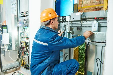 electrician worker adjusting equipment in elevator lift Archivio Fotografico