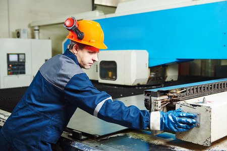sheet metal: Industrial worker operator of metal bending and punching machine at factory