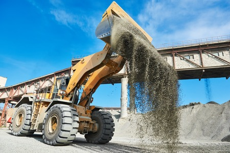 wheel loader: Mining industry. heavy wheel loader loading granite rock or ore at crushing and sorting plant