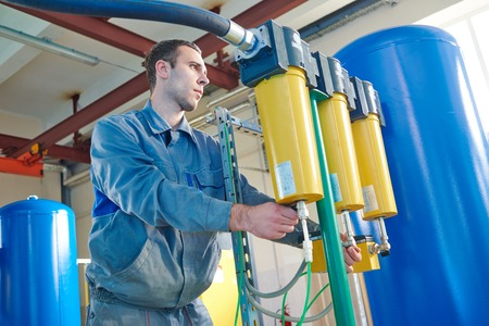 serviceman: Worker serviceman operating industrial water purification filtration equipment in boiler room or treatment plant