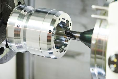 Przemysł metaloplastyka. Wielu narzędzie tnące CNC pefroming technologii pogłębiania i metalowych detali na tokarce wiercenia w fabryce. nastrojony