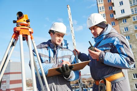 teodolito: dos constructores de regimen de trabajo con el equipo teodolito en el sitio de construcción Foto de archivo