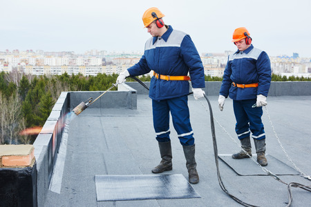 Flat roof installation. builders workers heating, melting and applying bitumen roofing felt by flame torch at construction site Archivio Fotografico