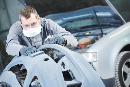 Auto body repairs. Repairman mechanic worker grinding automobile car bonnet by sand paper in garage workshop Standard-Bild