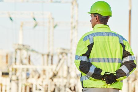 supervision: supervisión de ingeniería. ingeniero de servicio masculino en ropa de alta visibilidad que refleja y sombrero de pie dura al aire libre en frente de la estación de calor del electropower