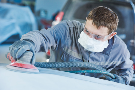 molinillo: reparaciones de carrocerías. Reparador del trabajador mecánico de molienda automóvil capo del coche por la amoladora en el taller en el garaje. tonificado