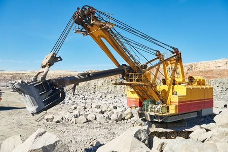 Heavy excavator extracting granite rock or iron ore at opencast mining quarry