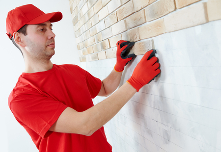facing a wall: interior wall facing decoration work with brick veneer installing by professional construction worker bricklayer at home indoors Stock Photo