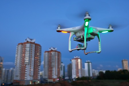 drone quadcopter with digital camera flying or hovering in evening blue sky over the city Stock Photo