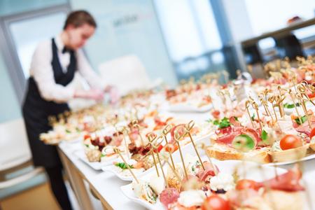 Servicio de catering o ocupación de camarero. Trabajadora de la camarera de trabajo sirviendo la mesa con platos de comida en la restauración en el restaurante. Someras DOF Foto de archivo
