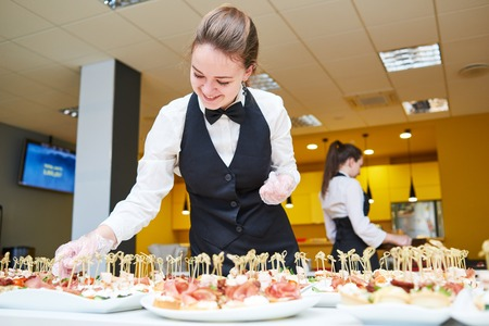 food industry: Restaurant service or waiter occupation. Female waitress worker serving table with food plates at catering in cafe