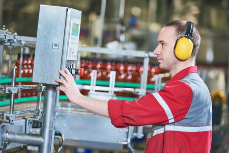 food and drink production industry. Factory worker operating conveyor for plastic bottles with beer or carbonated beverage moving
