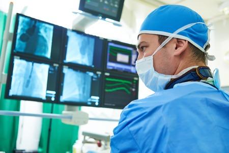 Intervenční kardiologie a radiologie. Muž chirurg lékař radiolog při provozu v průběhu léčby na bázi katetru s vizualizací X-ray.