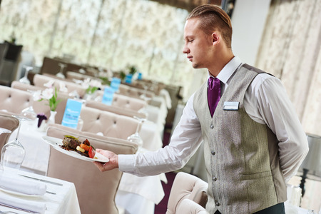 Restaurant service or waiter occupation. Handsome male worker serving table with food plates at catering in cafe Stock Photo
