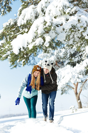 warm clothing: happy young couple people in warm clothing smiling and having fun at winter snow outdoors