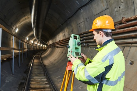 subway station: Surveyor worker with theodolite transit level equipment at underground railway tunnel subway construction work