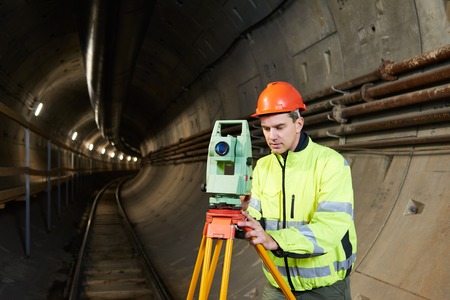 tacheometer: Surveyor worker with theodolite transit level equipment at underground railway tunnel subway construction work