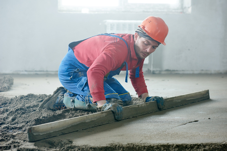 builder worker screeding indoor cement floor with screed at construction site