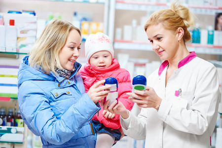 pharmacist chemist woman demonstrating vitamin to child girl with mother in pharmacy drugstore. family health Stock Photo
