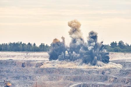 Przemysł wydobywczy. Wielki wybuch wybuch na ziemi do wydobywania skał granitowych rudy metali żelaza w kopalni odkrywkowej kamieniołomu Zdjęcie Seryjne