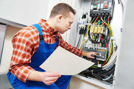test equipment: electrician with electric test screwdriver checking voltage of switching electric actuator equipment in fuse box