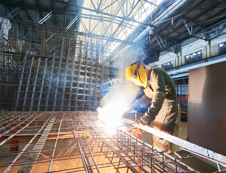 industrial welder worker at the factory arc welding process with sparks. Focus on sparkle. Worker blurred intentionally Stock Photo