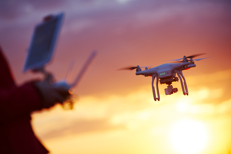 piloting flying copter drone at sunset Stockfoto