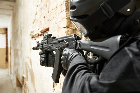 antiterrorist: Military industry. Special forces or anti-terrorist police soldier armed with assault rifle ready to attack during clean-up operation. Focus on assault rifle. Stock Photo