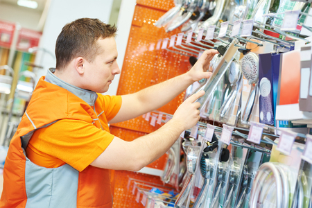 seller or shop assistant in hardware supermarket store arranging goods Stock Photo