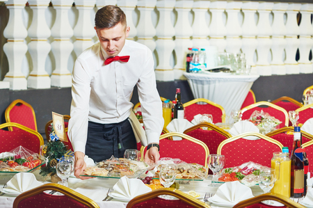 hotel staff: waitress occupation. Young woman with food on dishes servicing in restaurant during catering the event