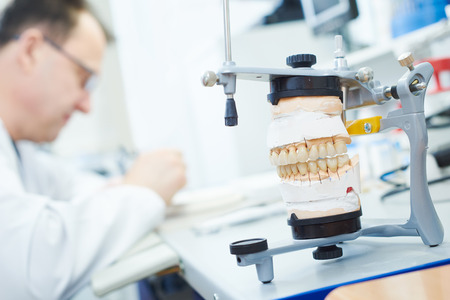 Dental technician painting tooth during work on dentures at prosthesis laboratory Stock Photo