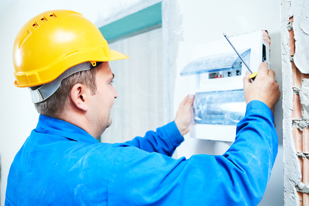 electrician with screwdriver installing switching electric actuators in fuse box