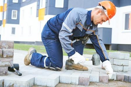 mason construction worker making sidewalk pavement or pedestrian way with stone blocks