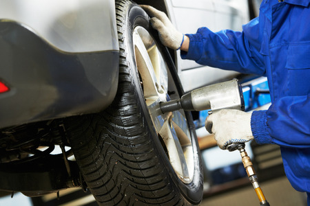 unscrewing: Automobile service. car mechanic screwing or unscrewing car wheel of lifted automobile by pneumatic wrench at repair station Stock Photo