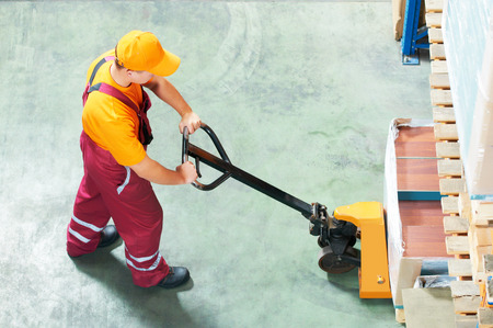 worker with fork pallet truck stacker in warehouse loading furniture panels photo