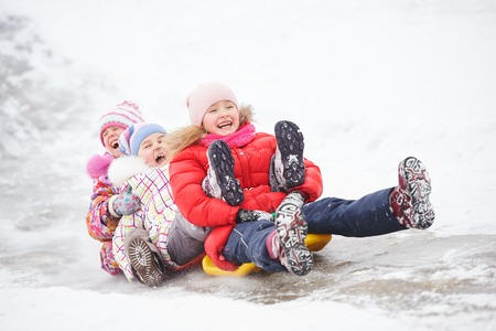 Children girls having fun in winter riding ice slide Stock Photo - 67153472