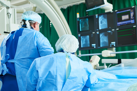 Interventional cardiology or radiology. Male surgeon doctor radiologist at operation during catheter based treatment with X-ray visualization.