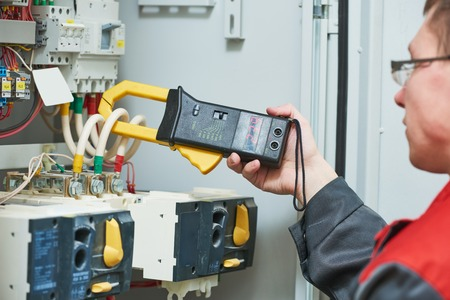Electrician works. male technician examining fusebox with digital clamp multimeter ac dc tester Archivio Fotografico