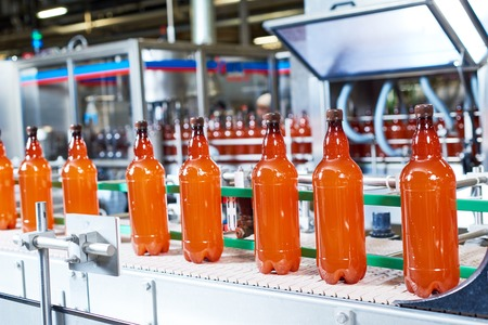 food and drink industry. Plastic bottles with beer or carbonated beverage moving on conveyor Stock Photo
