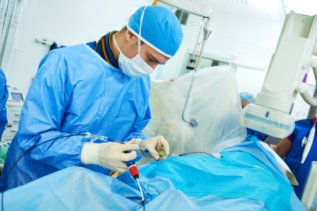 myocardial: Interventional cardiology or radiology. Male surgeon doctor radiologist at operation during catheter based treatment with X-ray visualization.