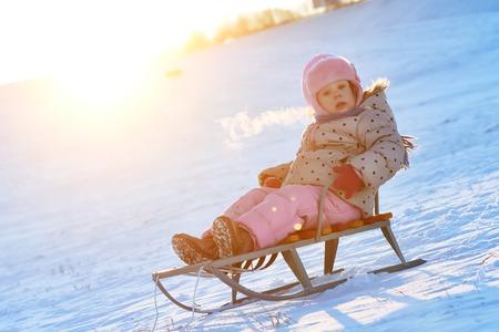 Happy children activity in winter. Girl sliding on sled