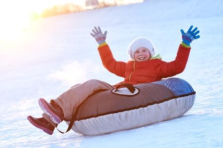 Happy children activity in winter. Girl sliding on sledding tubing Stock Photo