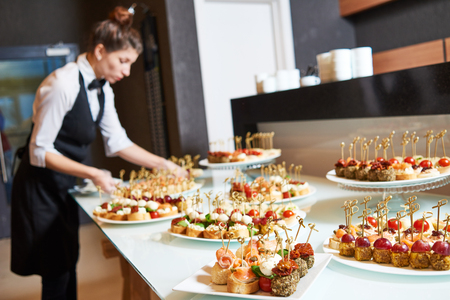 Restaurant service or waiter occupation. Female waitress worker serving table with food plates at catering in cafe