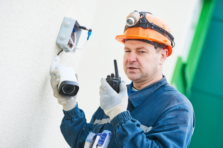 Video surveillance. Technician worker agjusting wall camera Zdjęcie Seryjne