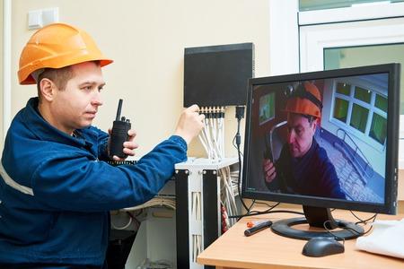Technicus werknemer agjusting positie en het signaal van video surveillance camera systeem Stockfoto