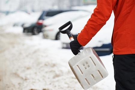 Nevado concepto de limpieza del coche. La mano con la pala en invierno