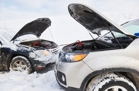 booster: Charging automobile discharged battery by booster jumper cables at winter Stock Photo