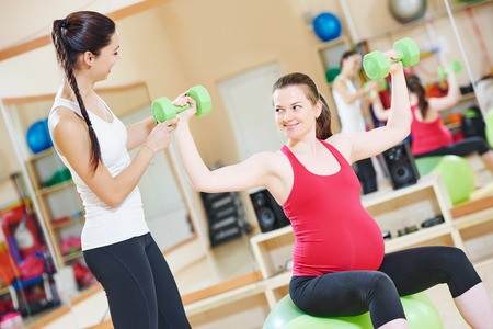 pregnant woman with instructor doing fitness ball exercise Stock Photo