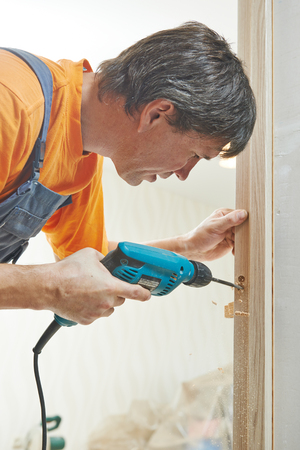 work from home: Carpenter works with drill Stock Photo